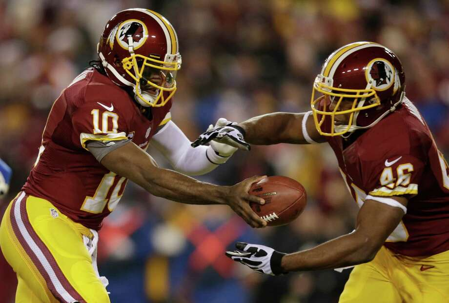 Washington Redskins quarterback Robert Griffin III (10) hands the ball off to running back Alfred Morris (46) during the first half of an NFL football game against the Dallas Cowboys Sunday, Dec. 30, 2012, in Landover, Md. (AP Photo/Evan Vucci) Photo: Evan Vucci, Associated Press / AP