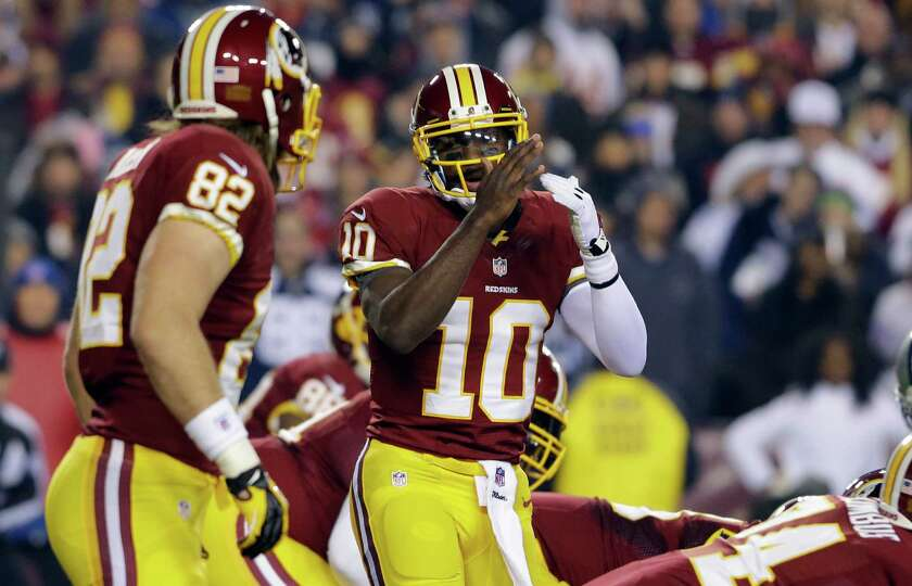 Washington Redskins quarterback Robert Griffin III calls timeout during the first half of an NFL foo