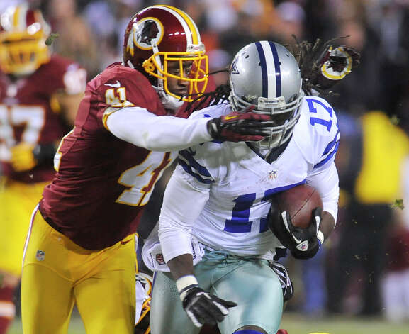 Washington Redskins free safety Madieu Williams (41) tackles Dallas Cowboys wide receiver Dwayne Harris (17) during the first half of an NFL football game Sunday, Dec. 30, 2012, in Landover, Md. (AP Photo/Richard Lipski) Photo: Richard Lipski, Associated Press / FR170623 AP