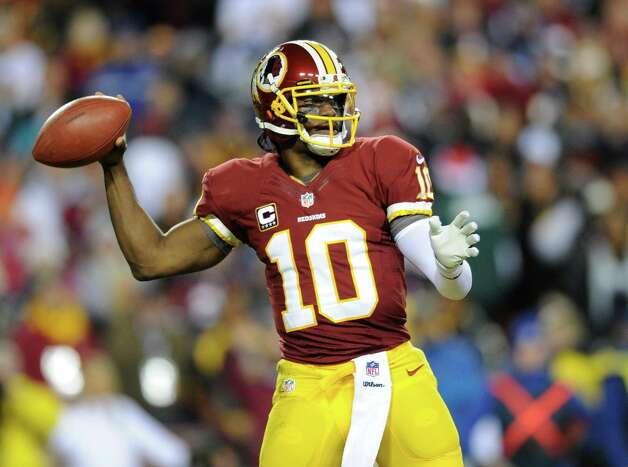Washington Redskins quarterback Robert Griffin III (10) looks to pass during the first half of an NFL football game against the Dallas Cowboys Sunday, Dec. 30, 2012, in Landover, Md. (AP Photo/Nick Wass) Photo: Nick Wass, Associated Press / FR67404 AP