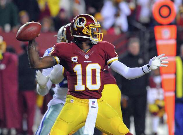 Washington Redskins quarterback Robert Griffin III (10) looks to pass during the first half of an NFL football game against the Dallas Cowboys Sunday, Dec. 30, 2012, in Landover, Md. (AP Photo/Richard Lipski) Photo: Richard Lipski, Associated Press / FR170623 AP