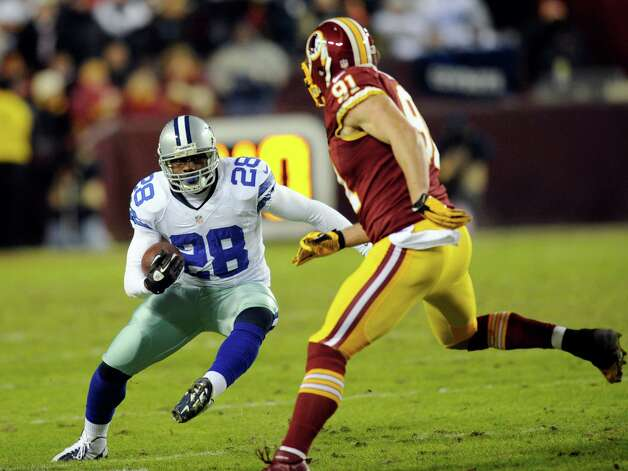 Dallas Cowboys running back Felix Jones (28) tries to avoid Washington Redskins outside linebacker Ryan Kerrigan (91) during the first half of an NFL football game Sunday, Dec. 30, 2012, in Landover, Md. (AP Photo/Nick Wass) Photo: Nick Wass, Associated Press / FR67404 AP