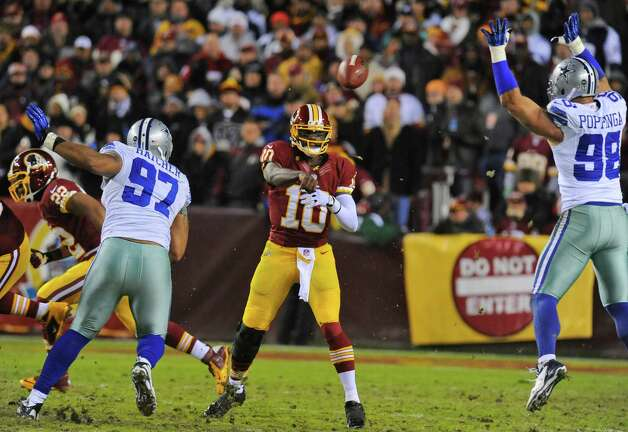 Washington Redskins quarterback Robert Griffin III (10) passes between Dallas Cowboys defensive end Jason Hatcher (97) and linebacker Brady Poppinga (98) during the first half of an NFL football game Sunday, Dec. 30, 2012, in Landover, Md. (AP Photo/Richard Lipski) Photo: Richard Lipski, Associated Press / FR170623 AP