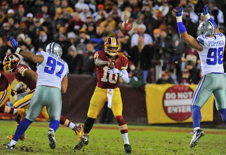 Washington Redskins quarterback Robert Griffin III (10) passes between Dallas Cowboys defensive end