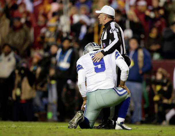 Dallas Cowboys quarterback Tony Romo (9) is helped up by referee Walt Anderson (66) during the first half of an NFL football game against the Washington Redskins Sunday, Dec. 30, 2012, in Landover, Md. (AP Photo/Evan Vucci) Photo: Evan Vucci, Associated Press / AP