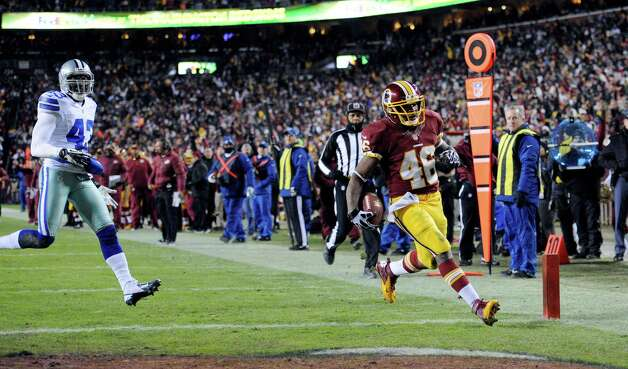 Washington Redskins running back Alfred Morris (46) outruns Dallas Cowboys free safety Gerald Sensabaugh (43) for a touchdown during the first half of an NFL football game Sunday, Dec. 30, 2012, in Landover, Md. (AP Photo/Nick Wass) Photo: Nick Wass, Associated Press / FR67404 AP