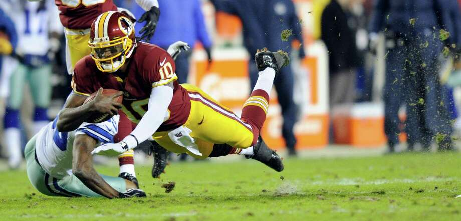 Washington Redskins quarterback Robert Griffin III (10) dives past Dallas Cowboys cornerback Brandon Carr (39) during the first half of an NFL football game Sunday, Dec. 30, 2012, in Landover, Md. (AP Photo/Nick Wass) Photo: Nick Wass, Associated Press / FR67404 AP
