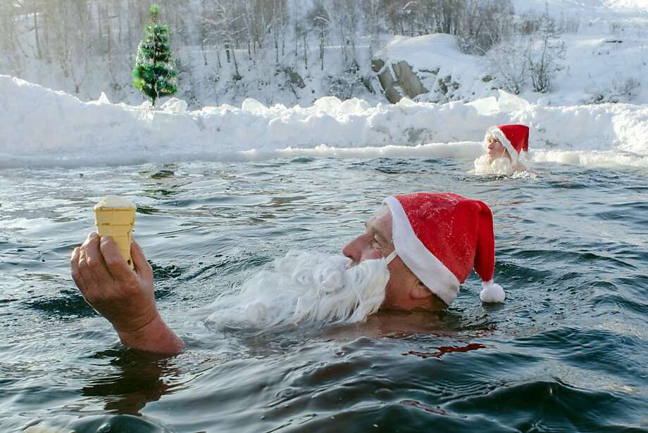 Vanilla float:A Russian Santa eyes an ice cream cone during a frigid swim in Novosibirsk, Siberia, but how is he going to eat it through that fake beard? Photo: Valery Titievsky, AFP/Getty Images