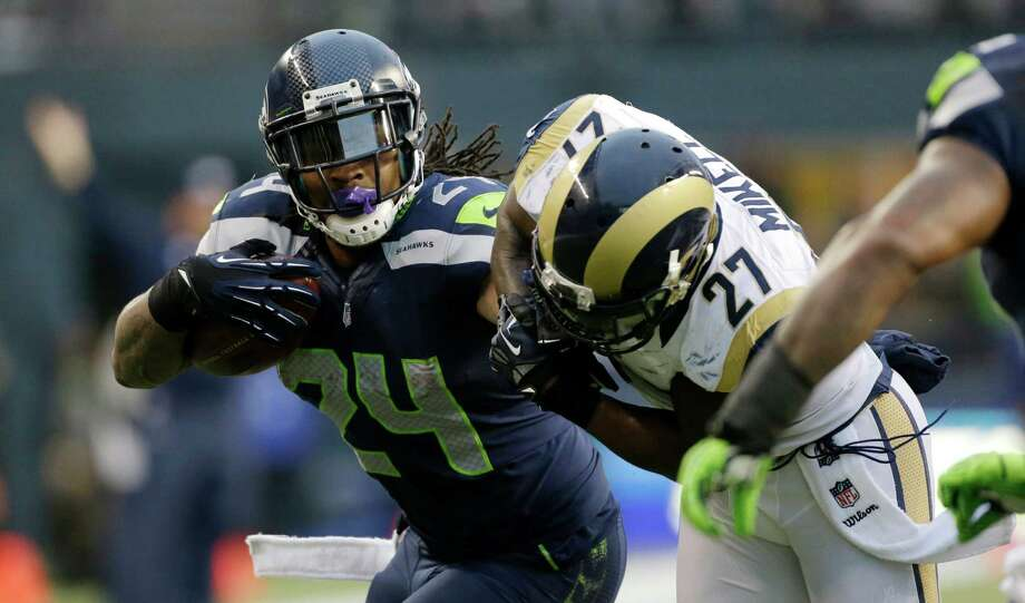 Seattle Seahawks' Marshawn Lynch, left, rushes against St. Louis Rams free safety Quintin Mikell, right, in the second half of an NFL football game, Sunday in Seattle. Photo: AP Photo/Elaine Thompson