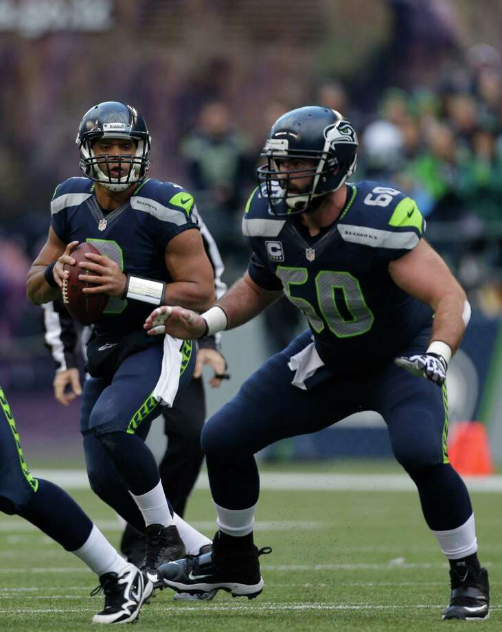 Seattle Seahawks quarterback Russell Wilson left, looks to pass as Seahawks' Max Unger (60) offers protection in the first half of an NFL football game, Sunday in Seattle. Photo: AP Photo/Elaine Thompson
