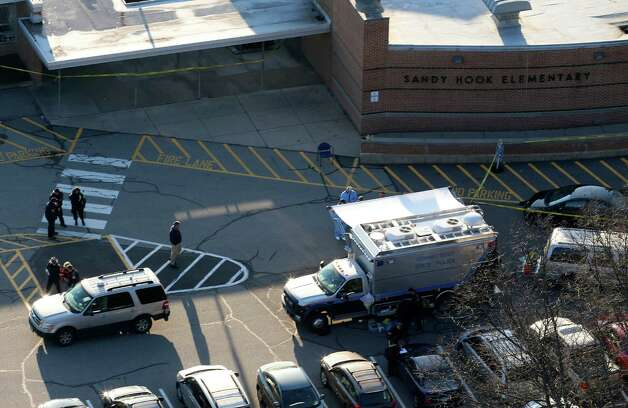 Officials are on the scene outside of Sandy Hook Elementary School in Newtown, Conn., where authorities say a gunman opened fire inside an elementary school in a shooting that left 26 people dead, including 20 children, Friday, Dec. 14, 2012. Photo: Julio Cortez, AP Photo/Julio Cortez / 2012 AP Associated Press