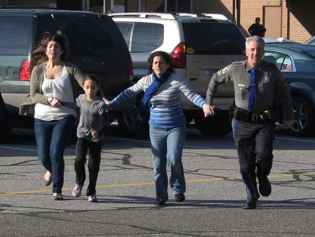In this photo provided by the Newtown Bee, a police officer leads two women and a child from Sandy Hook Elementary School in Newtown, Conn., where a gunman opened fire, killing 26 people, including 20 children, Friday, Dec. 14, 2012. Photo: Shannon Hicks, AP Photo/Newtown Bee, Shannon Hi / AP2012 Associated Press