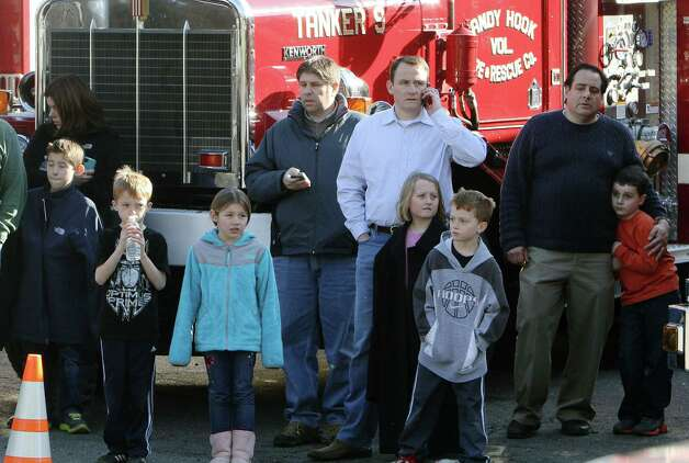 School children wait for their parents at the Sandy Hook firehouse following a mass shooting at the Sandy Hook Elementary School in Newtown, Conn. that left 26 dead on Friday, Dec. 14, 2012. Photo: Frank Becerra Jr., AP Photo/The Journal News, Frank / The Journal News 2012 Associated Press