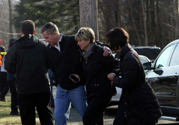 Teachers walk away from the Sandy Hook School following a shooting  at the school, Friday, Dec. 14, 2012 in Newtown, Conn. A man opened fire inside the Connecticut elementary school where his mother worked Friday, killing 26 people, including 18 children, and forcing students to cower in classrooms and then flee with the help of teachers and police. Photo: Frank Becerra Jr., AP Photo/The Journal News, Frank / The Journal News 2012 Associated Press