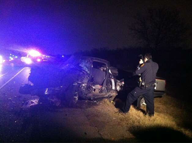 A San Antonio police officer photographs a pickup that collided with another truck, head-on, on the South Side Sunday night, Dec. 30, 2012. Both drivers were suspected of driving while intoxicated, officials said. Photo: Eva Ruth Moravec, San Antonio Express-News