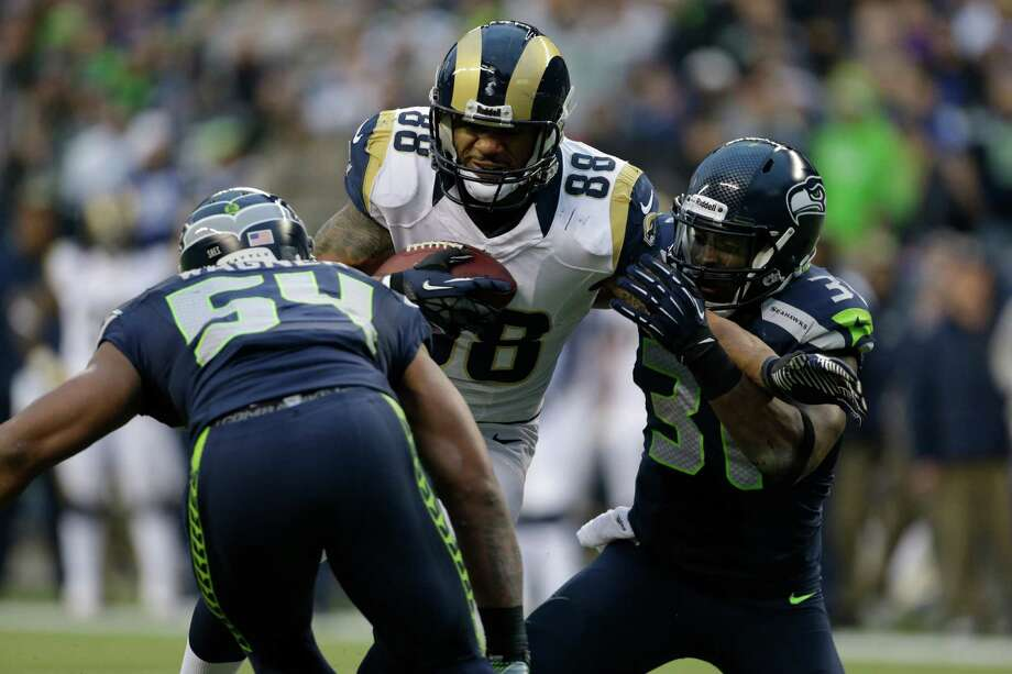 St. Louis Rams' Lance Kendricks rushes against Seattle Seahawks' Bobby Wagner (54) and Kam Chancellor, right, in the second half of an NFL football game, Sunday in Seattle. Photo: AP Photo/Elaine Thompson