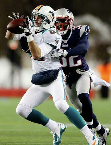 Miami Dolphins wide receiver Brian Hartline (82) catches a pass in front of New England Patriots free safety Devin McCourty (32) during the second quarter of an NFL football game in Foxborough, Mass., Sunday, Dec. 30, 2012. (AP Photo/Elise Amendola) Photo: Elise Amendola