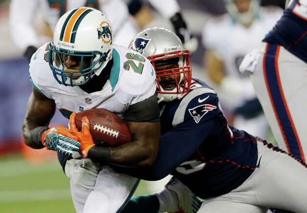 New England Patriots defensive end Chandler Jones, right, tackles Miami Dolphins running back Lamar Miller (26) during the first quarter of an NFL football game in Foxborough, Mass., Sunday, Dec. 30, 2012. (AP Photo/Elise Amendola) Photo: Elise Amendola