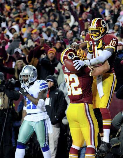 Washington Redskins quarterback Robert Griffin III (10) celebrates his touchdown with tight end Loga