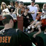 Giants catcher Buster Posey signs autographs for fans before playing in his first Cactus League spring training game against the Cincinnati Reds in Scottsdale, Ariz. on Friday, March 9, 2012.