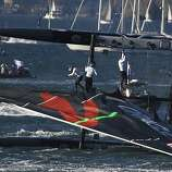 Crew members hang on after Oracle Team USA Spithill capsized in the first fleet race of the America's Cup World Series in San Francisco, Calif. on Saturday, Oct. 6, 2012.