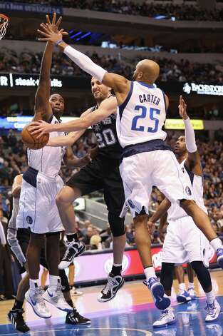 Manu Ginobili (20) of the Spurs takes a shot against the Mavs' Vince Carter (25) and Elton Brand (42) on Sunday in Dallas. Photo: Ronald Martinez, Getty Images / 2012 Getty Images