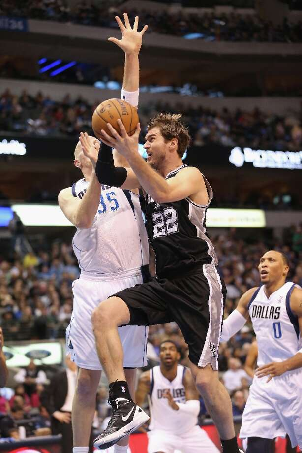 Tiago Splitter (22) of the Spurs takes a shot against Chris Kaman (35) of the Mavericks on Sunday in Dallas. Photo: Ronald Martinez, Getty Images / 2012 Getty Images