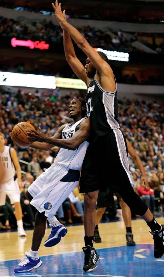 Mavericks guard Darren Collison (left) goes for a shot against pressure from Spurs forward Tim Duncan during the first half in Dallas on Sunday, Dec. 30, 2012. Photo: Mike Fuentes, Associated Press / FR103746 AP
