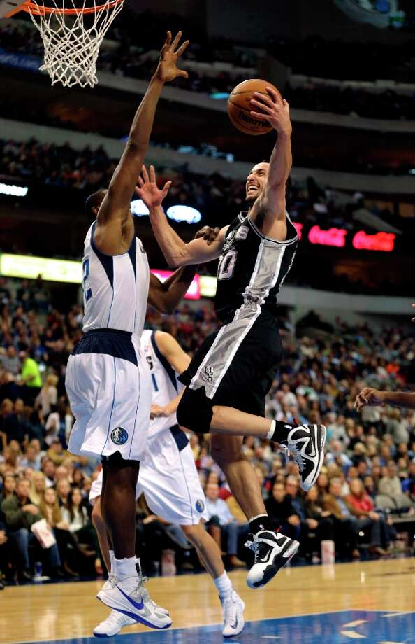 Spurs guard Manu Ginobili (right) attempts a shot against Mavericks defender Elton Brand during the second half game in Dallas on Sunday, Dec. 30, 2012. San Antonio won 111-86. Photo: Mike Fuentes, Associated Press / FR103746 AP