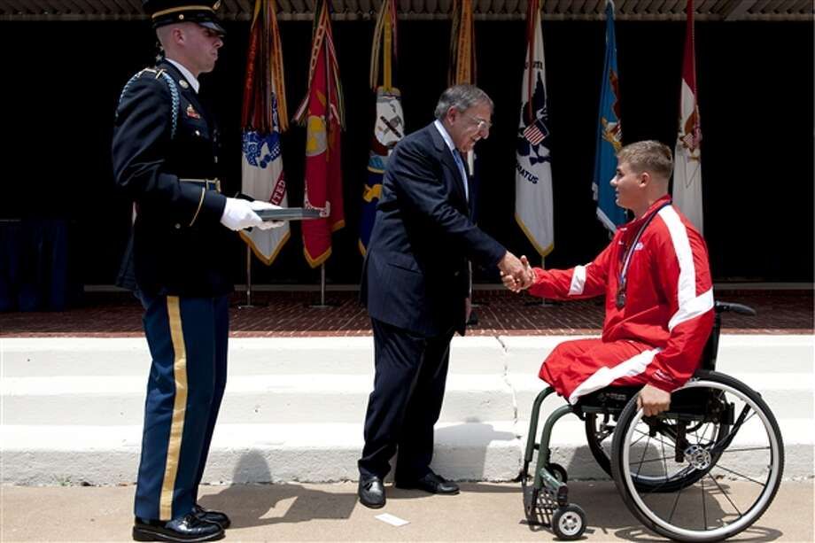 Defense Secretary Leon E. Panetta congratulates Marine Corps Lance Cpl. Ronald Sullivan at the 2012 Warrior Games. Sullivan is to be the recipient of a new home being built in Schertz by the Helping A Hero organization. Photo: Department Of Defense Courtesy P