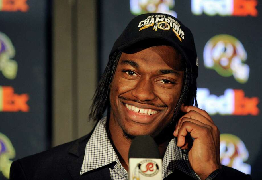 Washington Redskins quarterback Robert Griffin III smiles as he wears a NFC East Division Champions hat after an NFL football game against the Dallas Cowboys Monday, Dec. 31, 2012, in Landover, Md. The Redskins won 28-18, securing a playoff berth. (AP Photo/Nick Wass) Photo: Nick Wass, Associated Press / FR67404 AP