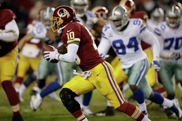Washington Redskins quarterback Robert Griffin III (10) runs with the ball during the second half of an NFL football game against the Dallas Cowboys Sunday, Dec. 30, 2012, in Landover, Md. (AP Photo/Evan Vucci) Photo: Evan Vucci, Associated Press / AP