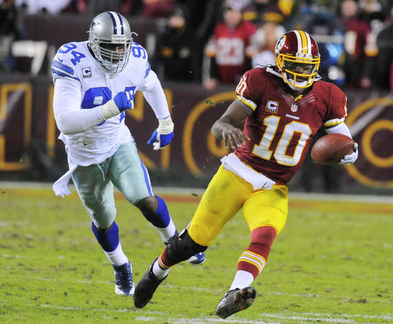 Washington Redskins quarterback Robert Griffin III (10) runs away from Dallas Cowboys outside linebacker DeMarcus Ware (94) during the second half of an NFL football game Sunday, Dec. 30, 2012, in Landover, Md. The Redskins won 28-18. (AP Photo/Richard Lipski) Photo: Richard Lipski, Associated Press / FR170623 AP