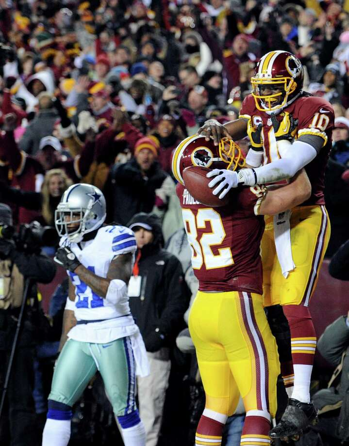 Washington Redskins quarterback Robert Griffin III (10) celebrates his touchdown with tight end Logan Paulsen (82) during the second half of an NFL football game against the Dallas Cowboys Sunday, Dec. 30, 2012, in Landover, Md. (AP Photo/Nick Wass) Photo: Nick Wass, Associated Press / FR67404 AP