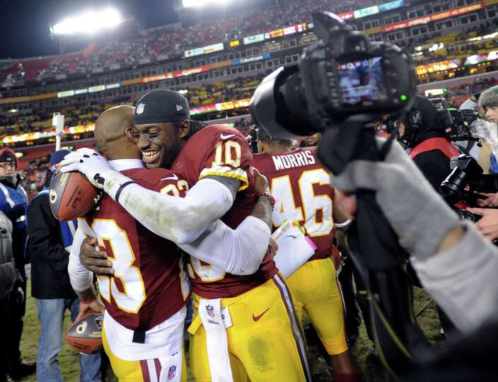 Washington Redskins cornerback DeAngelo Hall (23) celebrates with quarterback Robert Griffin III (10