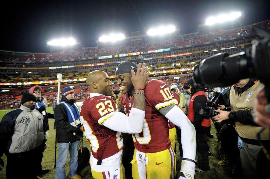 Washington Redskins cornerback DeAngelo Hall (23) celebrates with Washington Redskins quarterback Robert Griffin III (10) after an NFL football game against the Dallas Cowboys Sunday, Dec. 30, 2012, in Landover, Md. The Redskins won 28-18, securing a playoff berth. (AP Photo/Nick Wass) Photo: Nick Wass, Associated Press / FR67404 AP