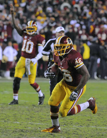Washington Redskins quarterback Robert Griffin III (10) reacts as running back Alfred Morris (46) heads for a touchdown during the second half of an NFL football game against the Dallas Cowboys on Sunday, Dec. 30, 2012, in Landover, Md. (AP Photo/Richard Lipski) Photo: Richard Lipski, Associated Press / FR170623 AP