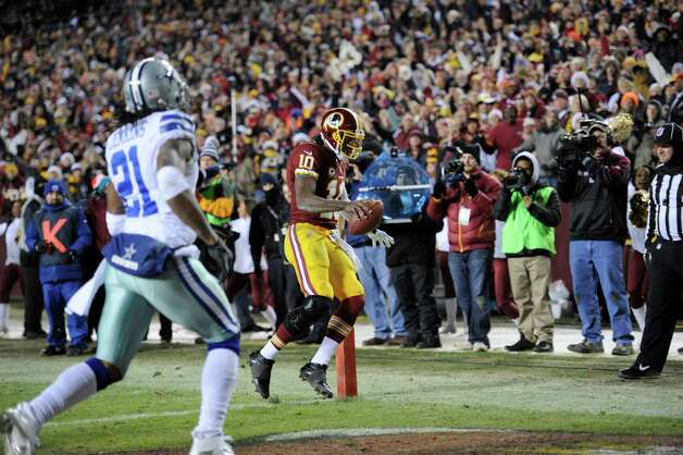 Washington Redskins quarterback Robert Griffin III (10) scores a touchdown in front of Dallas Cowboys cornerback Mike Jenkins (21) during the second half of an NFL football game Sunday, Dec. 30, 2012, in Landover, Md. (AP Photo/Nick Wass) Photo: Nick Wass, Associated Press / FR67404 AP