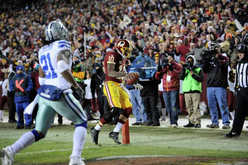 Washington Redskins quarterback Robert Griffin III (10) scores a touchdown in front of Dallas Cowboy