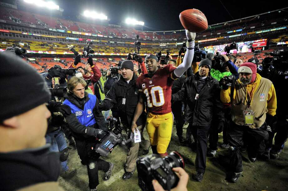 Washington Redskins quarterback Robert Griffin III (10) celebrates as he comes off the field after an NFL football game against the Dallas Cowboys Sunday, Dec. 30, 2012, in Landover, Md. The Redskins won 28-18, securing a playoff berth. (AP Photo/Nick Wass) Photo: Nick Wass, Associated Press / FR67404 AP