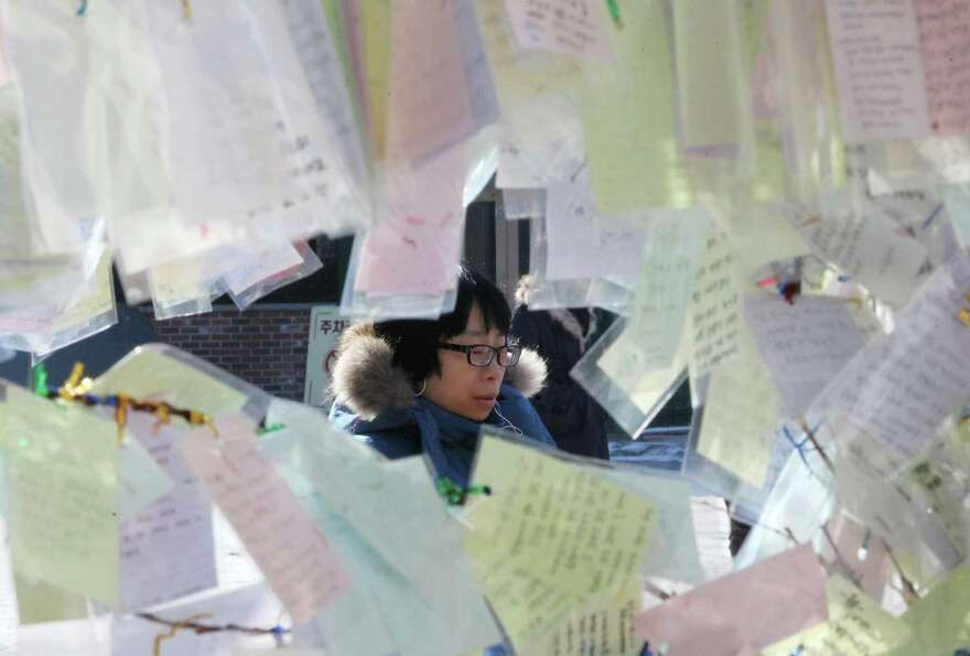 A Catholic prays behind papers, bearing New Year wishes, tied to trees at Myeongdong Catholic Cathed