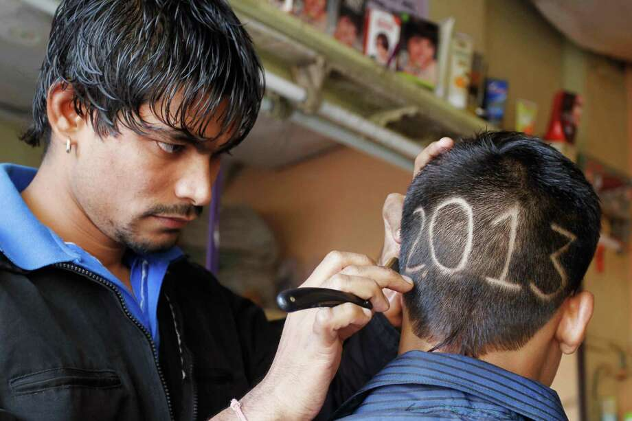 An Indian barber gives finishing touches to the hairstyle of a young boy with numbers to welcome the new year in Ahmadabad, India. Photo: Ajit Solanki