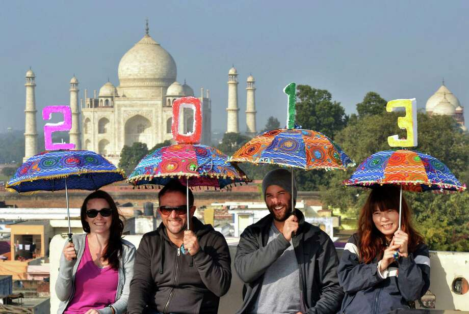 Tourists pose as they carry umbrellas with numbers to welcome the year 2013 on the terrace of a hotel in the backdrop of the Taj Mahal in Agra, India. Photo: Pawan Sharma