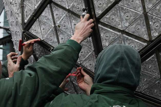 NEW YORK, NY - DECEMBER 27:  Workers install new Waterford Crystal triangles on the Times Square New Years Eve Ball at a media event on December 27, 2012 in New York City. The ball will once again descend a 141-foot tall flagpole to mark the beginning of 2013. Photo: Mario Tama, Getty Images / 2012 Getty Images