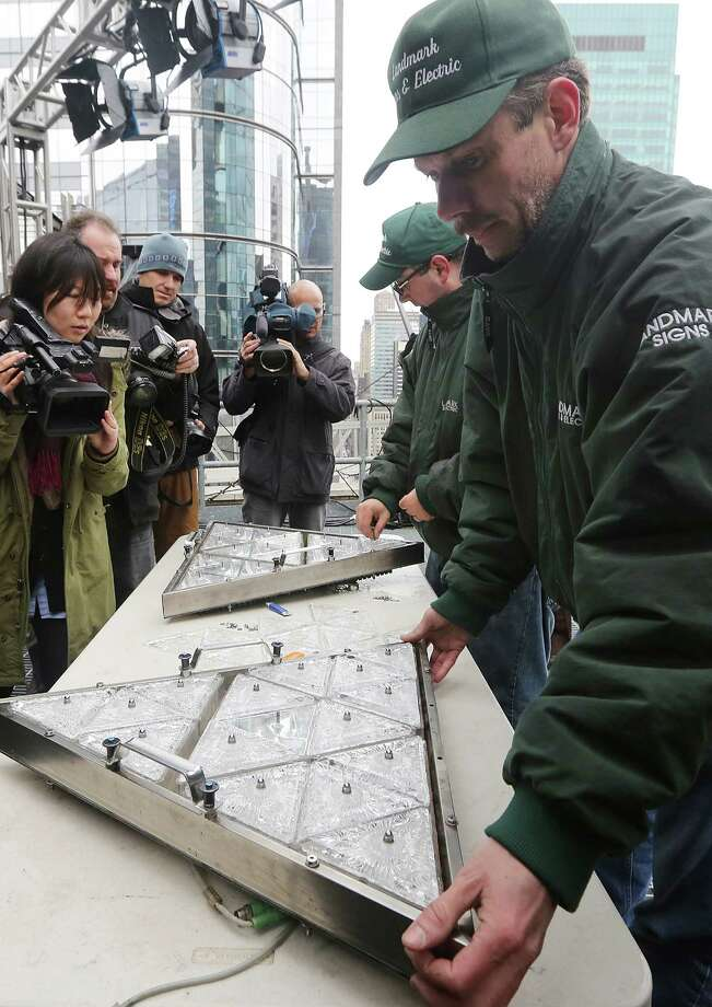 NEW YORK, NY - DECEMBER 27:  Workers stand with new Waterford Crystal triangles on the Times Square New Years Eve Ball at a media event on December 27, 2012 in New York City. The ball will once again descend a 141-foot tall flagpole to mark the beginning of 2013. Photo: Mario Tama, Getty Images / 2012 Getty Images