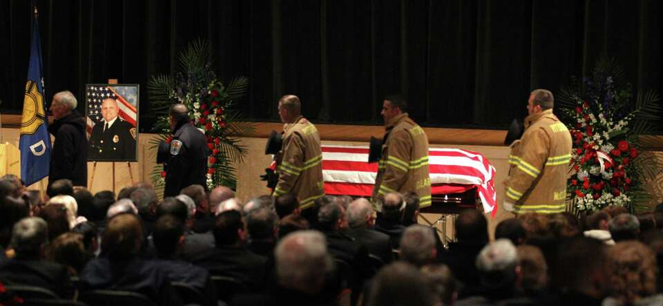 Emergency responders pass by the casket of firefighter Michael Chiapperini during his  funeral servi