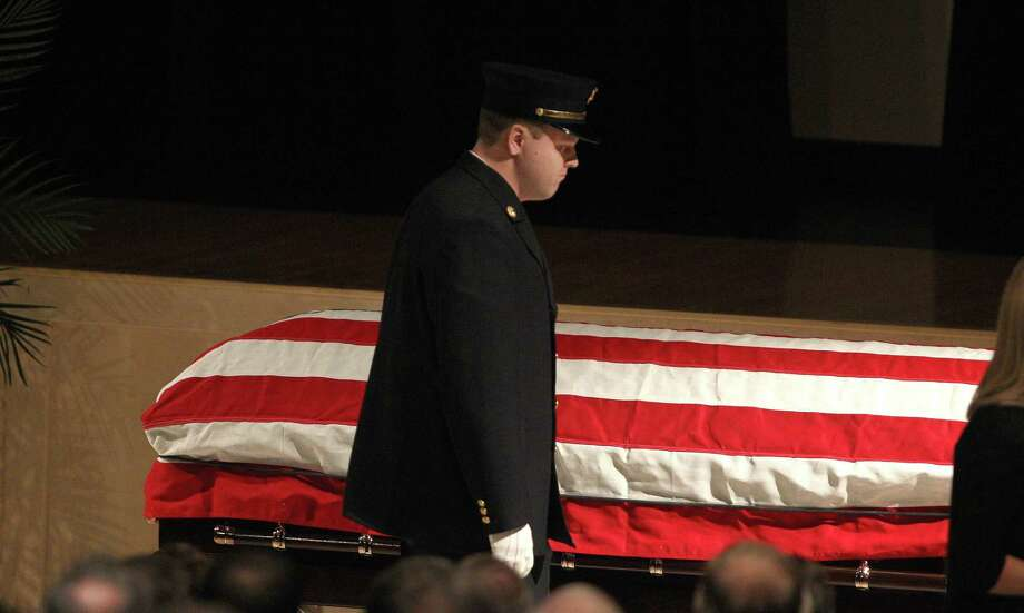 Nick Chiapperini, son of  firefighter Michael Chiapperini, walks past the casketduring his father's funeral service, Sunday Dec. 30, 2012 at Webster Schroeder High School in Webster, N.Y. Thousands of mourners, including firefighters from across the United States and Canada payed their final respects to West Webster Fire Fighter, Lt. Michael Chiapperini. Chiapperini and firefighter, Tomasz Kaczowka, were both shot and killed while on duty Dec. 24, 2012 in Webster, N.Y. Photo: Jamie Germano, AP / POOL Democrat & Chronicle