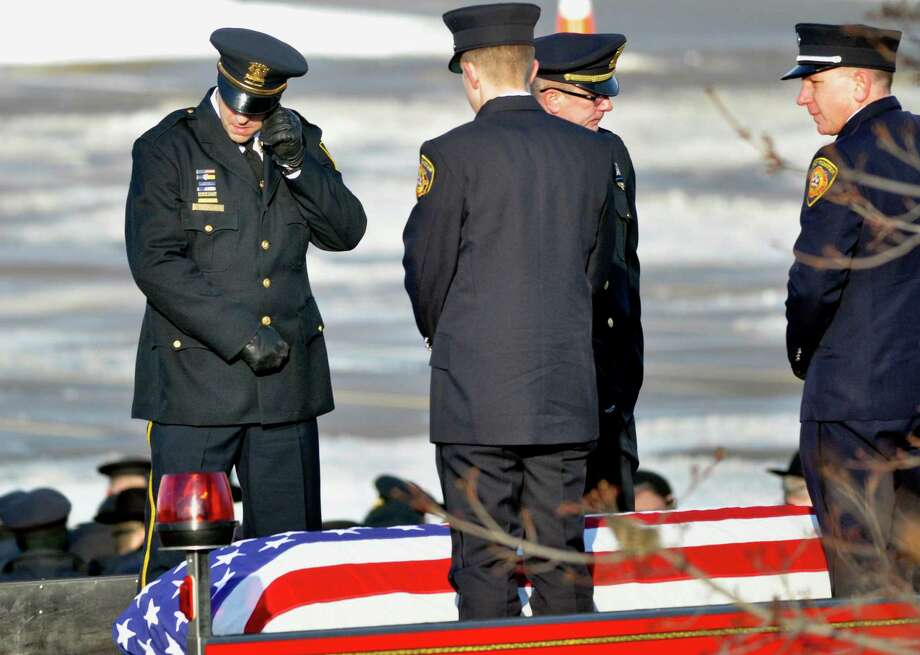 A firefighter, left, wipes away tears during the funeral service for Lt. Mike Chiapperini in Webster, N.Y., Sunday, Dec. 30, 2012. Chiapperini, 43, and fellow firefighter Tomasz Kaczowka, 19, were slain by gunman William Spengler in a fiery Christmas Eve ambush in a neighborhood on the shore of Lake Ontario. Two other firefighters remain hospitalized with bullet wounds. Photo: Kevin Rivoli, AP / FR60349 AP