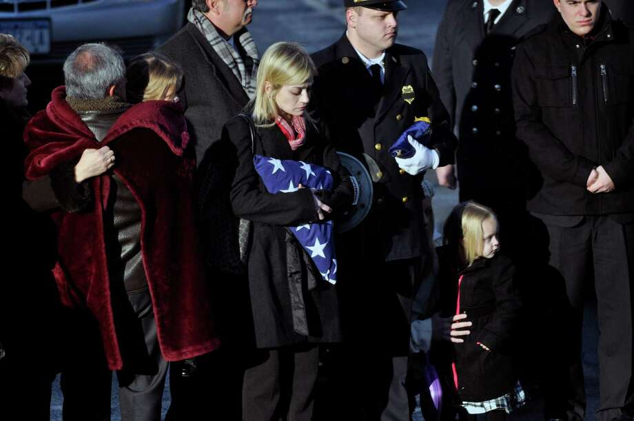 Kimberly Chiapperini, center, clutches the American flag presented to her during a funeral service for her husband Lt. Mike Chiapperini in Webster, N.Y., Sunday, Dec. 30, 2012. Chiapperini, a volunteer firefighter, was fatally shot as he arrived at a house fire set by the ex-convict who later killed himself. Also pictured are Chiapperni's daughter, Kacie, left, son Nicholas, behind Kimberly, and Kylie, lower right. Photo: KEVIN RIVOLI, AP / FR60349 AP