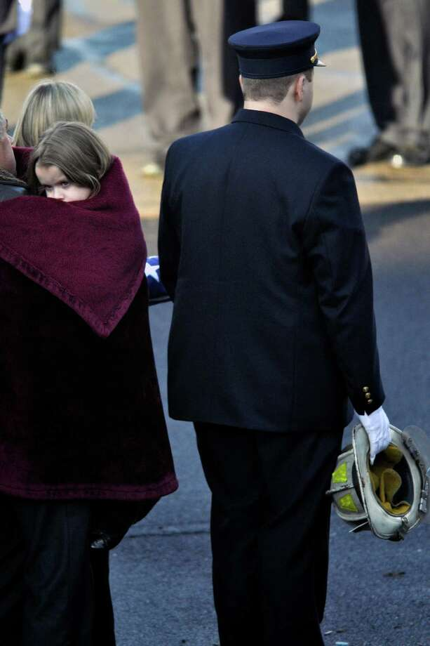 Nicholas Chiapperini holds his father's, Lt. Mike Chiapperini, helmet as sister Kacie looks on during a funeral service in Webster, N.Y., Sunday, Dec. 30, 2012. Mike Chiapperini, a volunteer firefighter, was fatally shot as he arrived at a house fire set by the ex-convict who later killed himself. Photo: KEVIN RIVOLI, AP / FR60349 AP